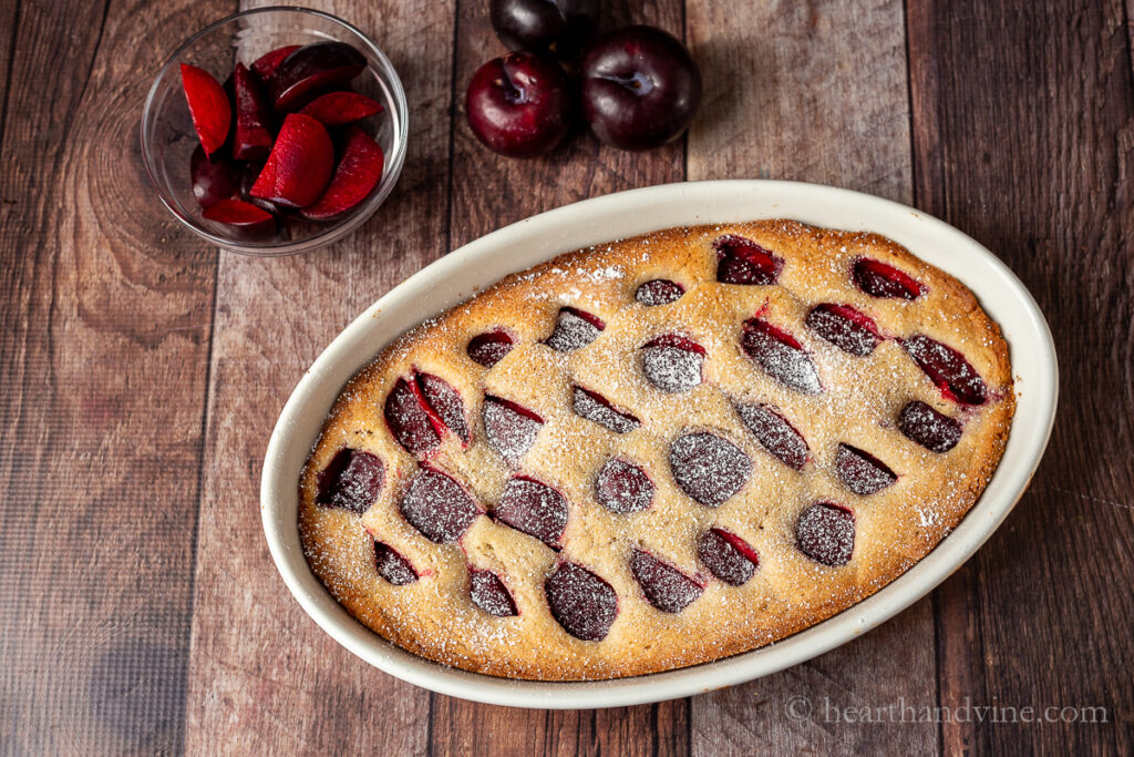 Oval ceramic pan with plum cake dusted with powdered sugar.