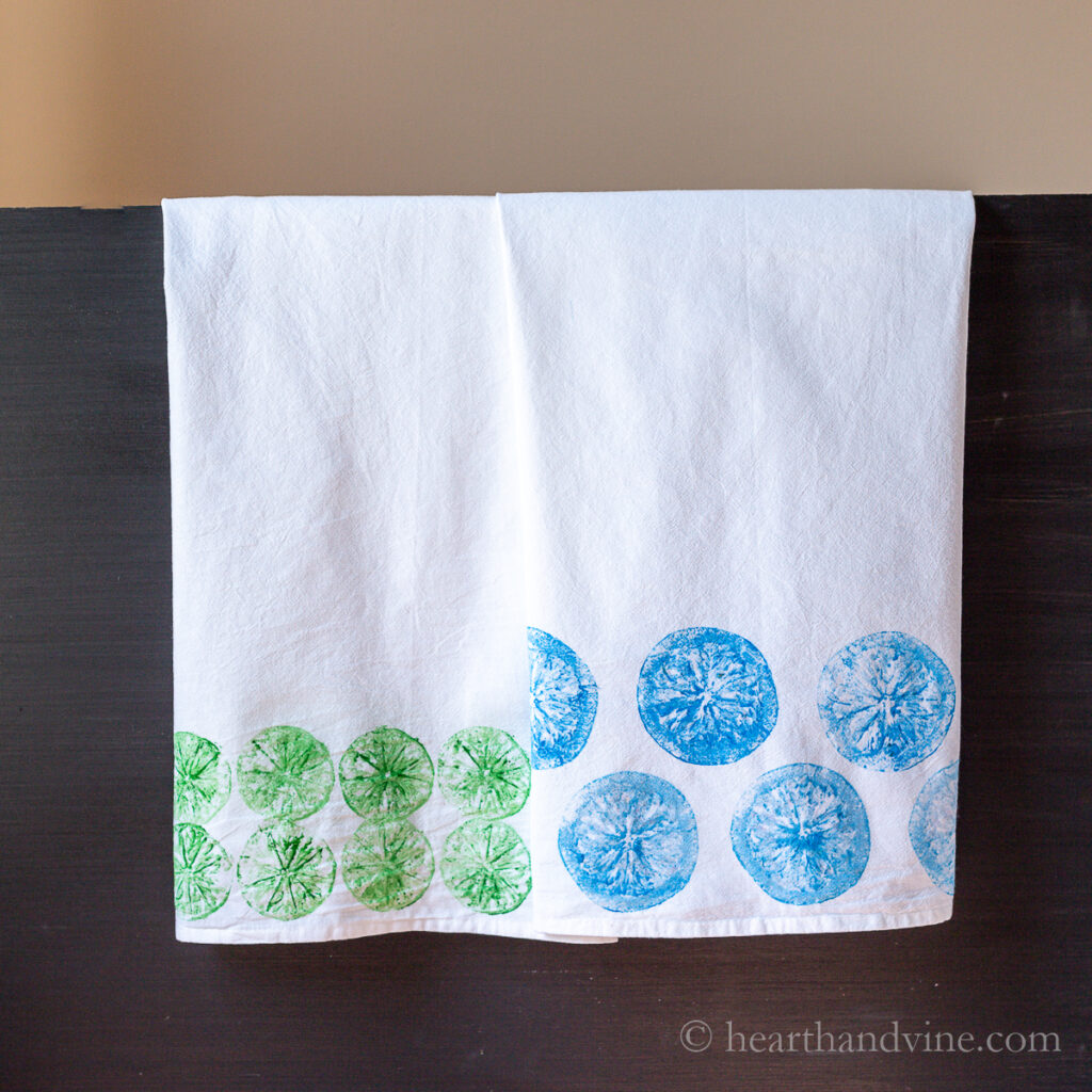 Two hand printed tea towels hanging. One is printed with green limes and the second is blue oranges.