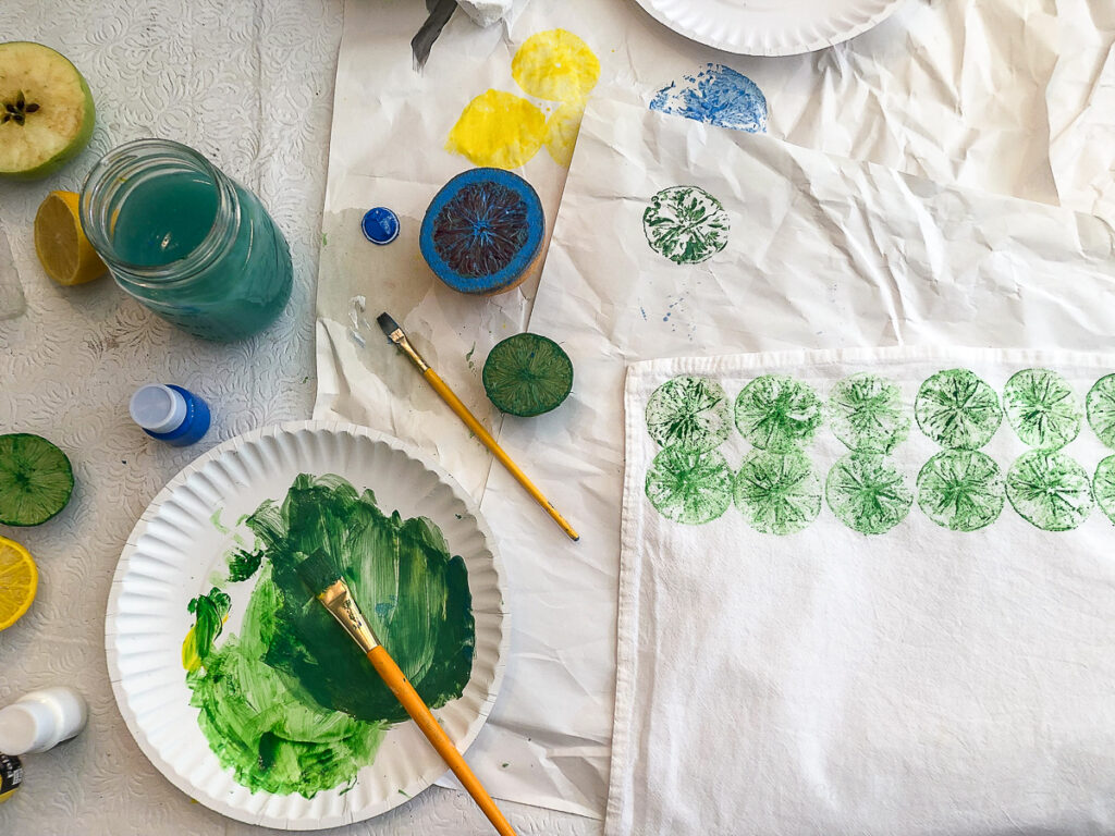 Image showing a workspace with a jar of water, paper plate with paint, a paintbrush and a tea towel with green lime prints.