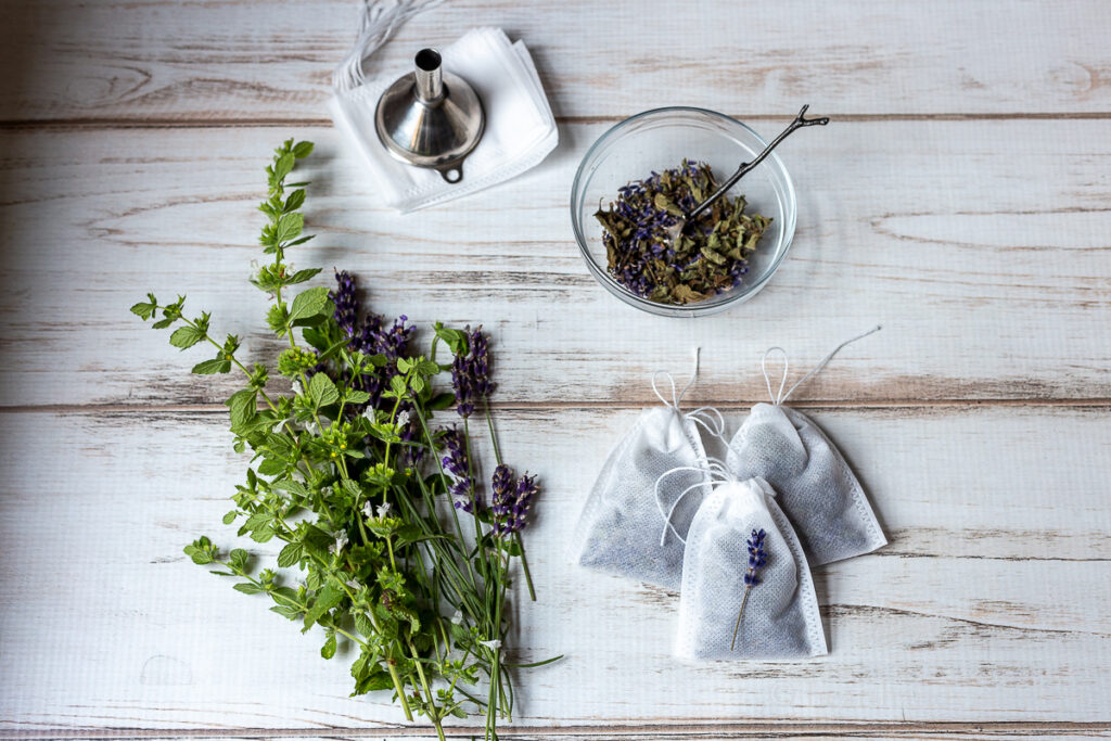 Fresh lavender and lemon balm, a bowl of dried lavender and lemon balm, three small herbal dream pillows, a funnel and white tea bags.