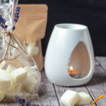Wax burner with wax melts in front along with lavender and lemon peel and bagged melts.