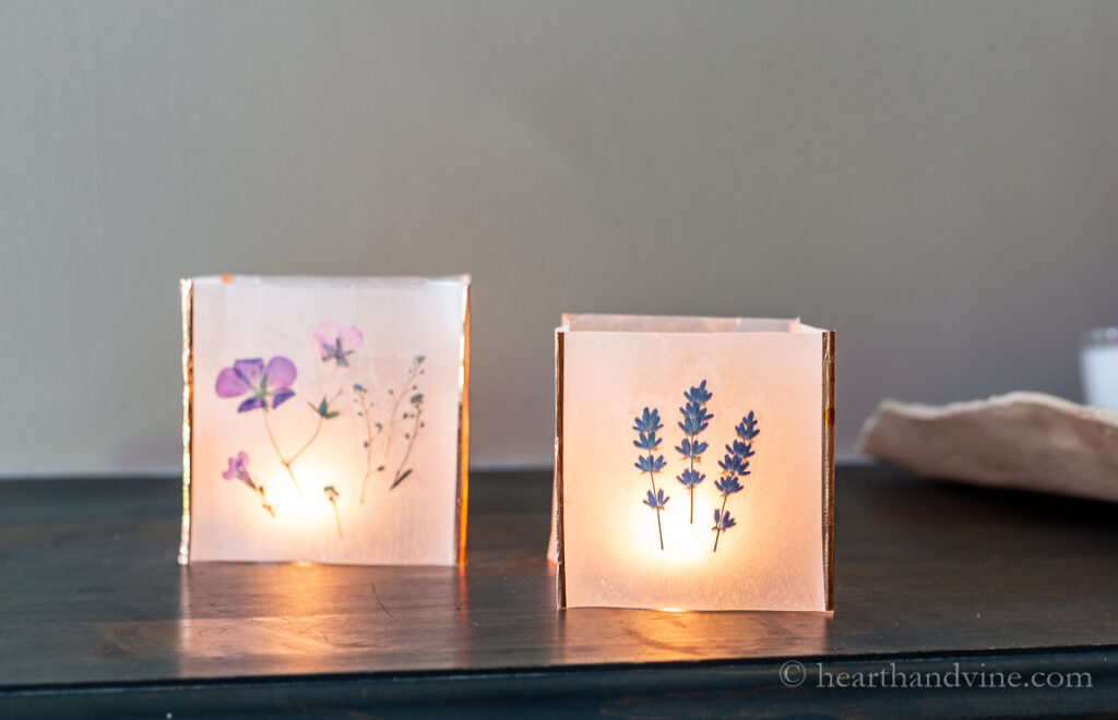 Two pressed flower luminaries with candles inside.