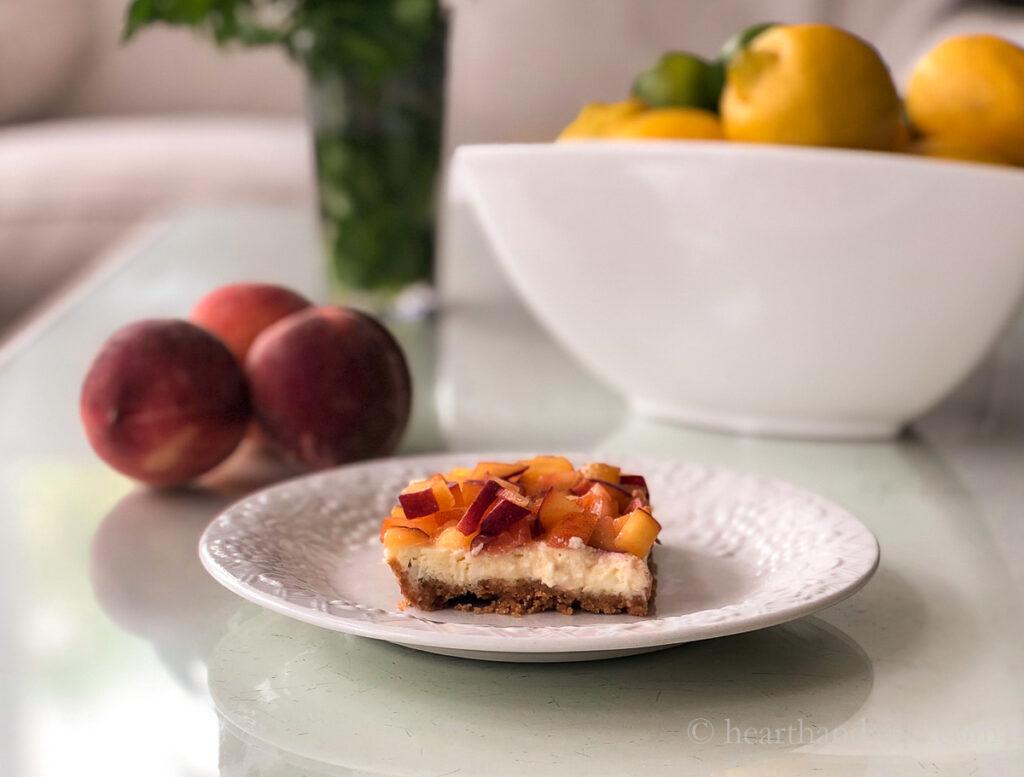 Lado da barra de cheesecake de pêssego servindo em um prato ao lado de três pêssegos inteiros.