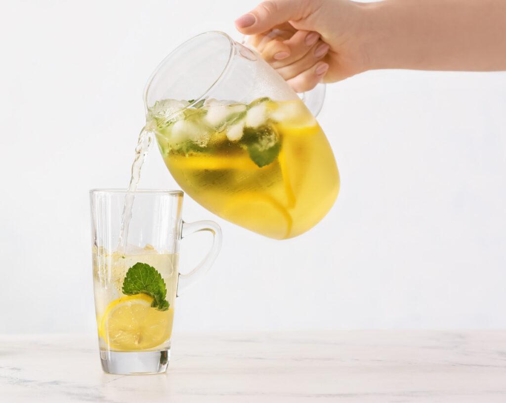 Mint tea with lemon poured into a glass.