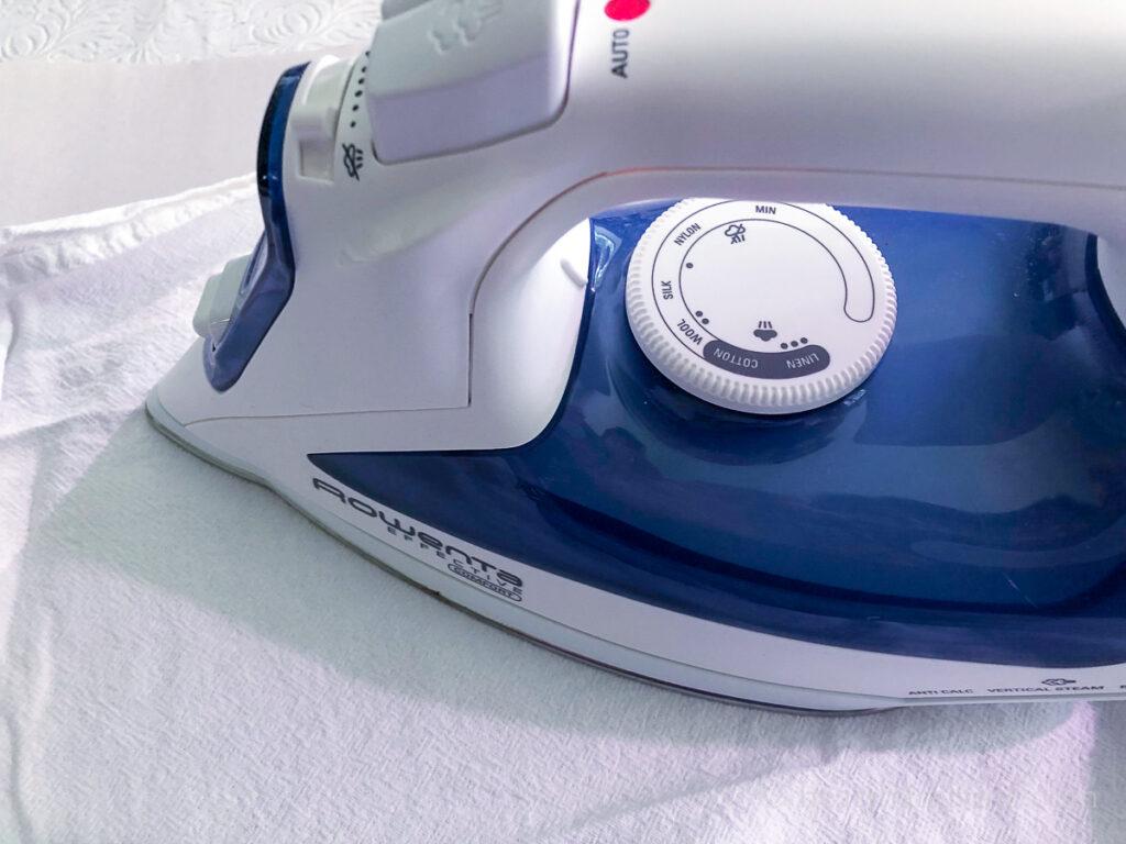 Iron pressing a white tea towel.