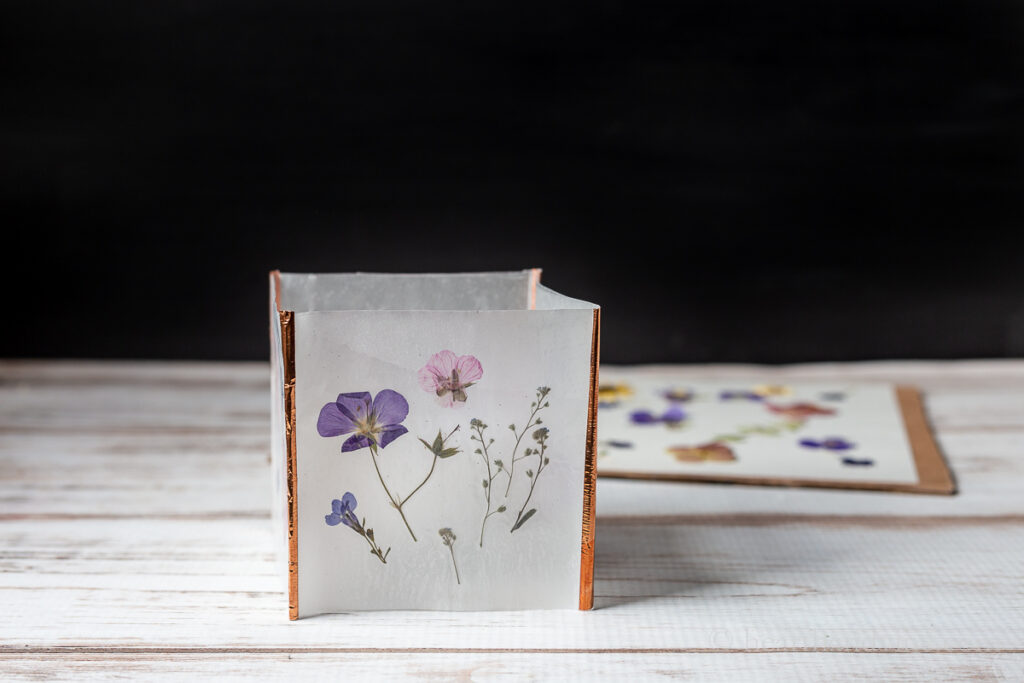 One pressed flower luminaria with copper tape edges.