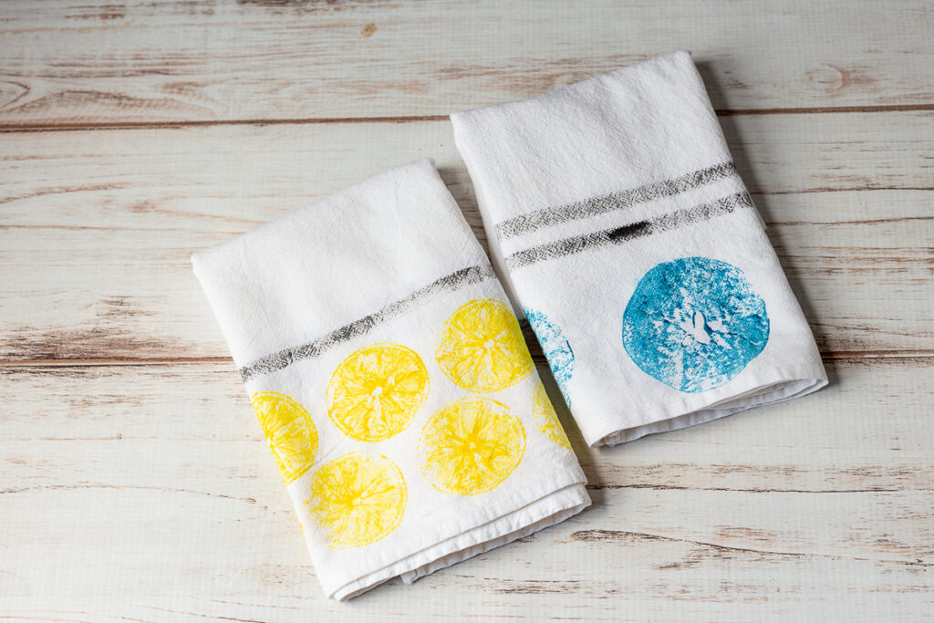 A lemon yellow print and an apple print in blue tea towel with black stripes on  a table.