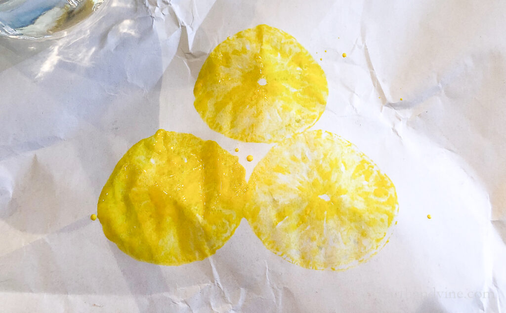 Three stamps lemons with yellow paint on paper showing the image after each print.