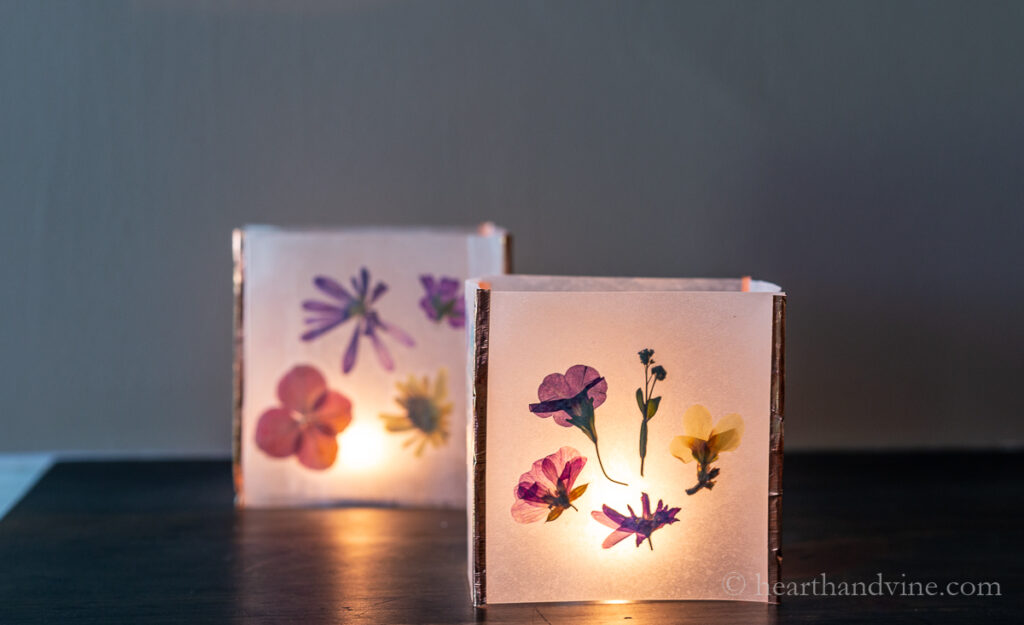 Two copper tape pressed flower luminaries with candles inside in a dark room.