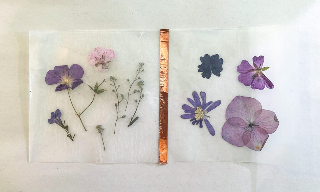 Two squares of pressed flowers between wax paper. A strip of copper tape holding to sides together.