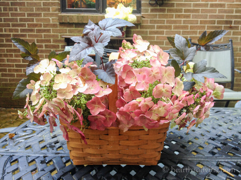 Wide wooden basket with pink hydrangea flowers and ninebark branches.