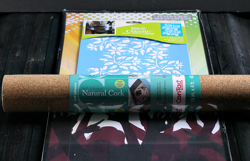 Cork contact paper roll on top of a floral stencil and poster frame.
