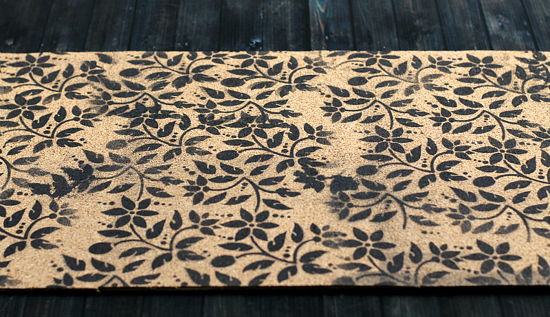 Stenciled cork with floral print in black paint.