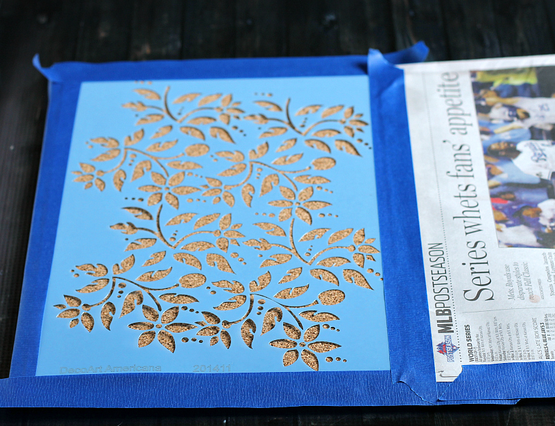 Leafy floral stencil taped to cork and newspaper covering the rest.