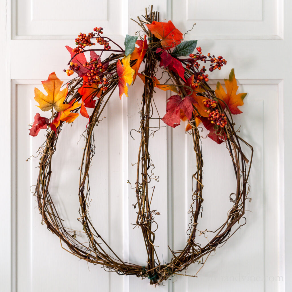 Grapevine wreath in a pumpkin shape with fall leaves and berries.