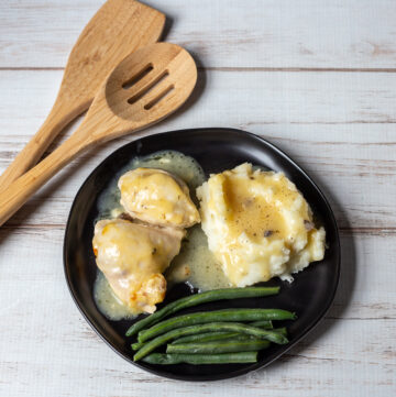 Baked creamy chicken dinner with mash potatoes and green beans on a plate.