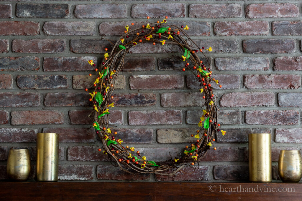 Mantel with gold candle holders on each side of a large autumn colored wreath with faux bittersweet berries.