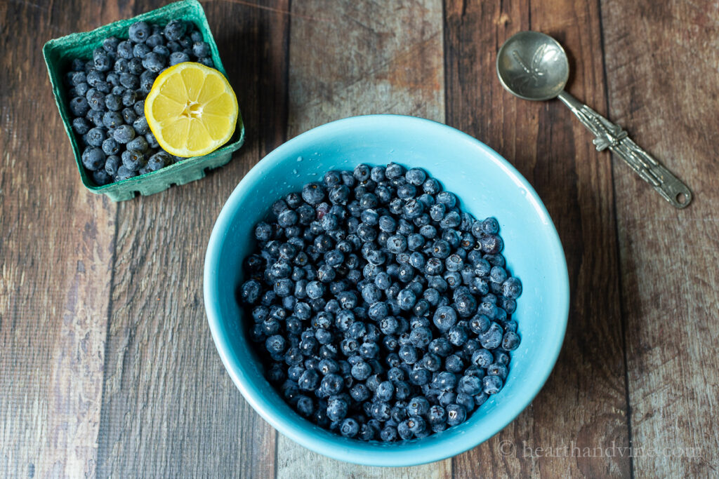 Bowl of fresh blueberries next to an ornate spoon and a cardboard pint of berries and half a lemon.