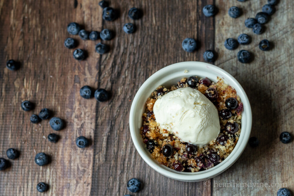 A white ramekin with blueberry Betty dessert and vanilla ice cream. Fresh blueberries are scattered around the table.
