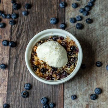 Blueberry betty in a ramekin with vanilla ice cream.