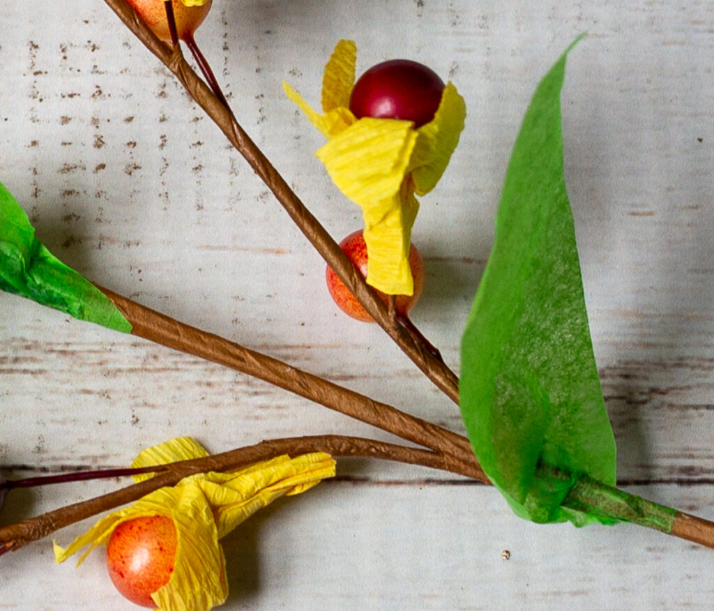 Close up look at crepe paper petals and tissue paper leaves on berry stem.