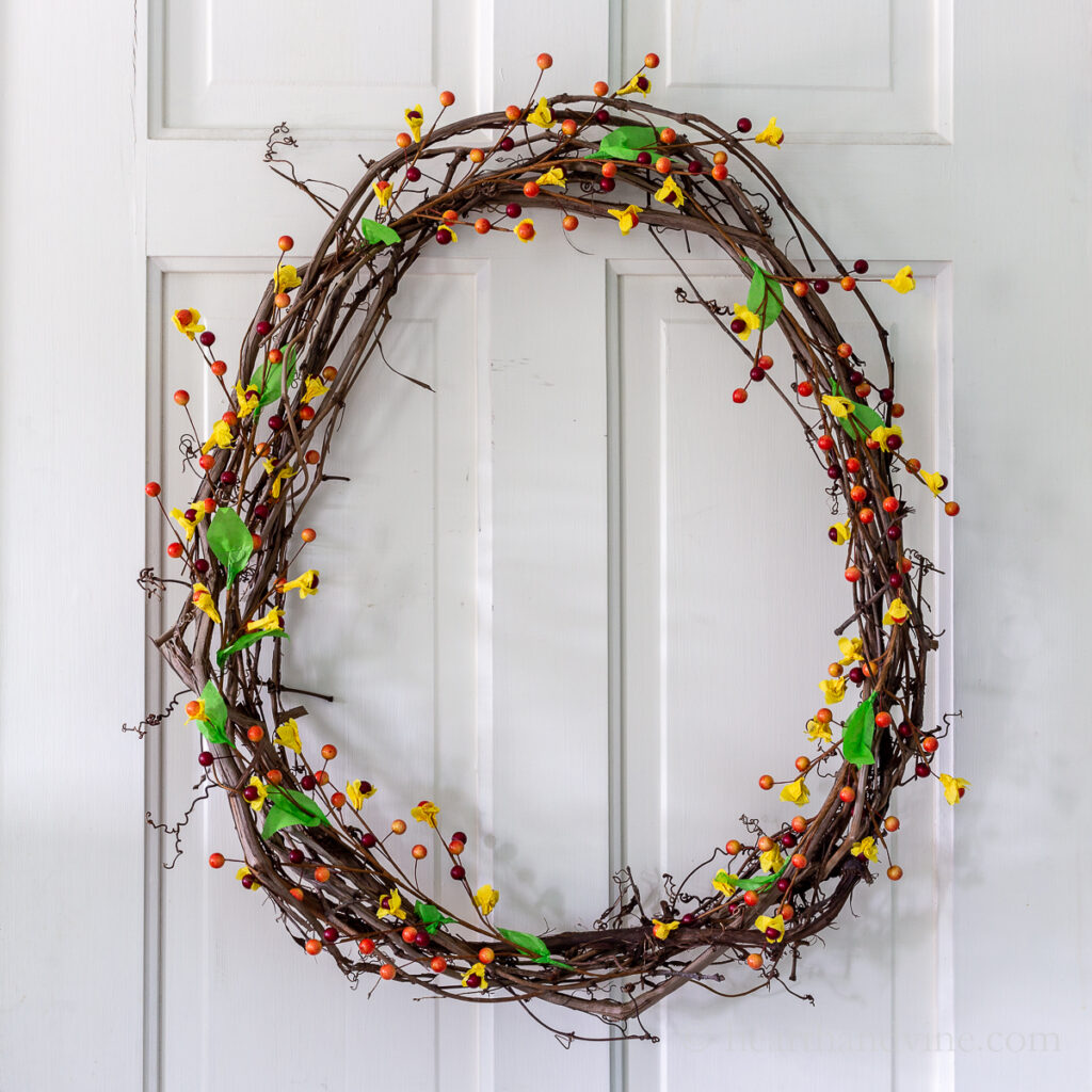 Grapevine wreath with artificial bittersweet looking berries on a white door.