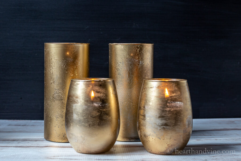 Four gold mercury glass candle holders with candles burning inside. Two in the front are rounded and short and the two in the back are taller and straight.