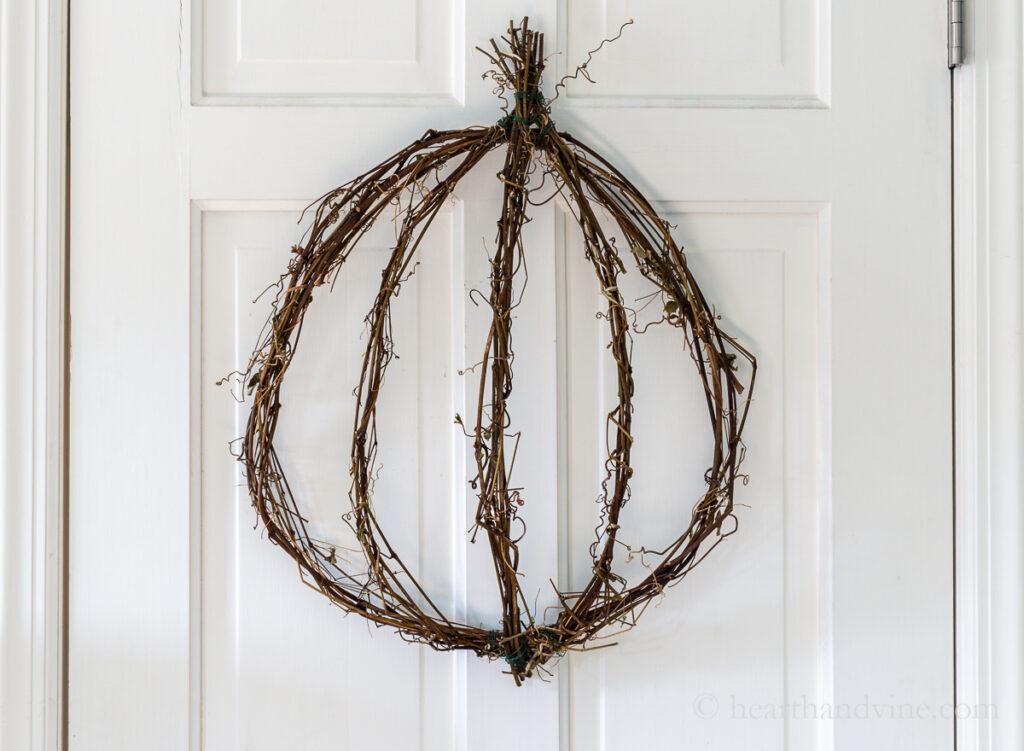 Grapevine pumpkin wreath on white door.