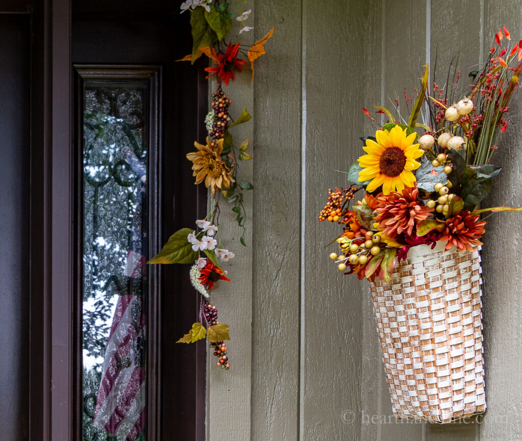 Basket of fall florals hanging on the side wall of front porch.