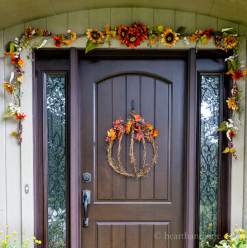 Fall decorated front door with a pumpkin wreath and fall garland