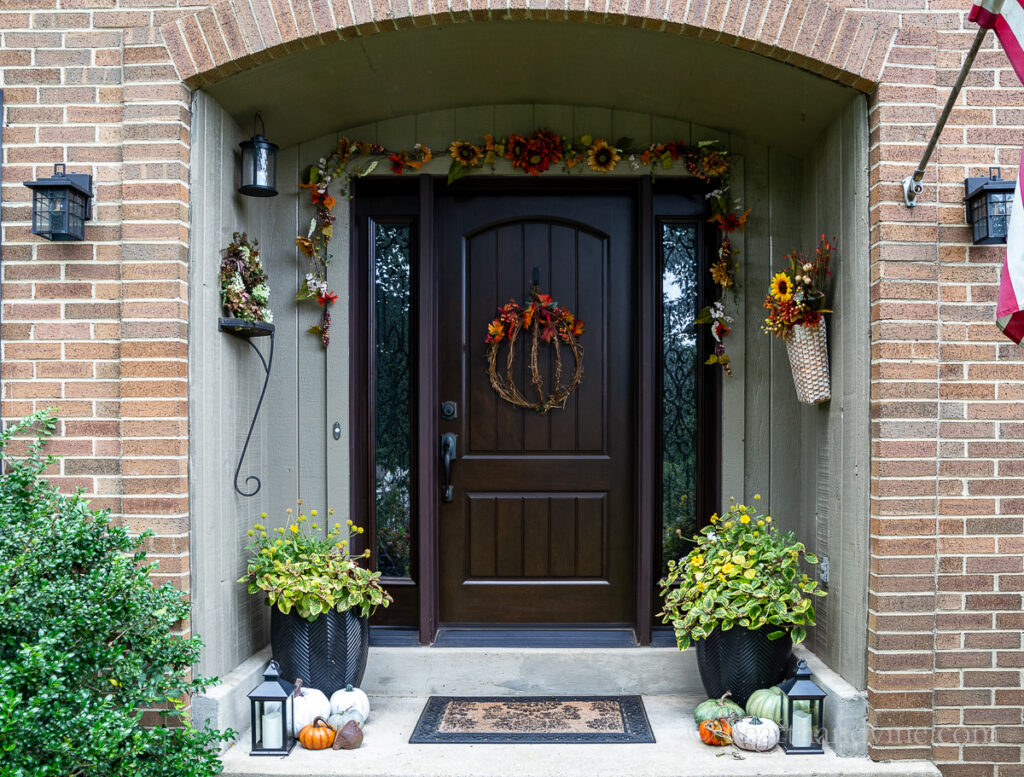 Front porch fall decor with a grapevine pumpkin wreath, fall flowers and pumpkins.