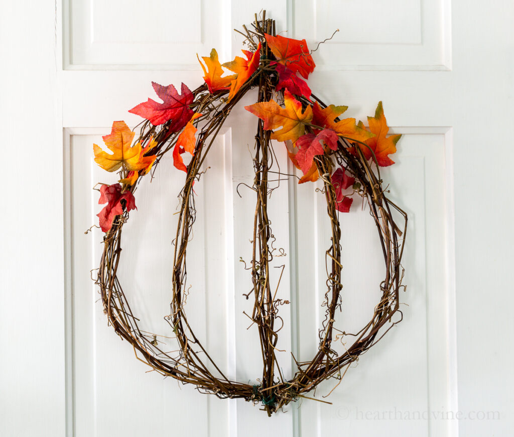 Pumpkin shaped grapevine wreath with fall leaves.