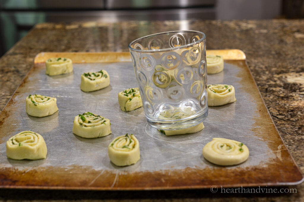 Puff pastry pinwheels on a cookie sheet and a glass flattening them.