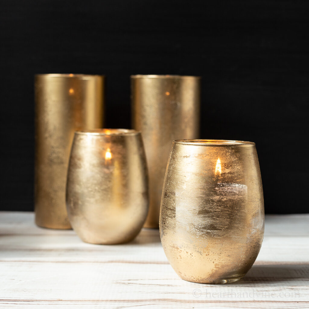Four gold mercury glasses with candles. Two rounded in front and two taller and  straight in the back.