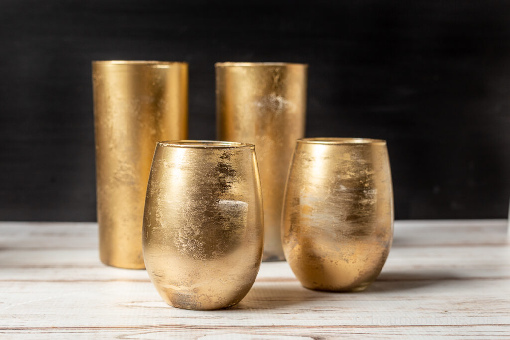 Four gold mercury glass candle holders. Two in the front are rounded and short and the two in the back are taller and straight.