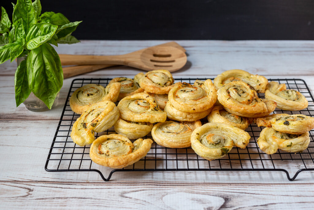 Baked puff pastry pinwheels on a cooling rack.