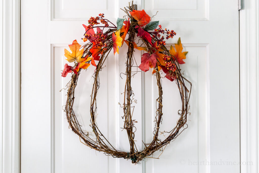 Grapevine pumpkin wreath decorating with fall leaves and berries.