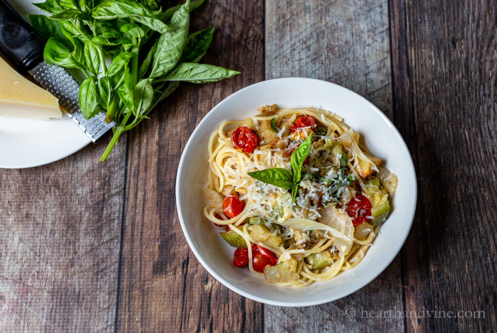 Small white bowl with roasted ratatouille pasta topped with grated Parmesan cheese.