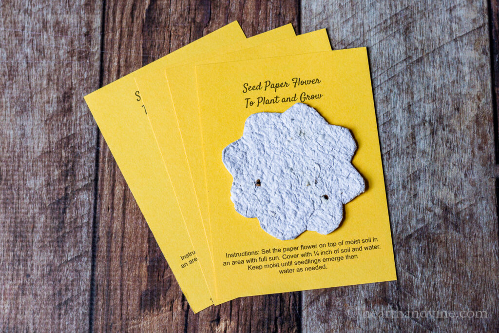 Yellow cards with a flower cut out of seed paper and instructions of how to plant it.