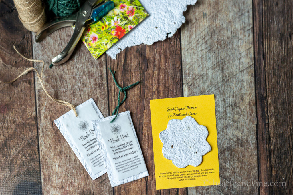 Seed paper thank you tags and flower cut out card next to twine, a paper punch and a packet of wildflower seeds.