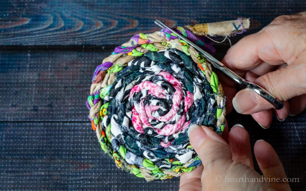 Trimming the end of a fabric twine coaster.