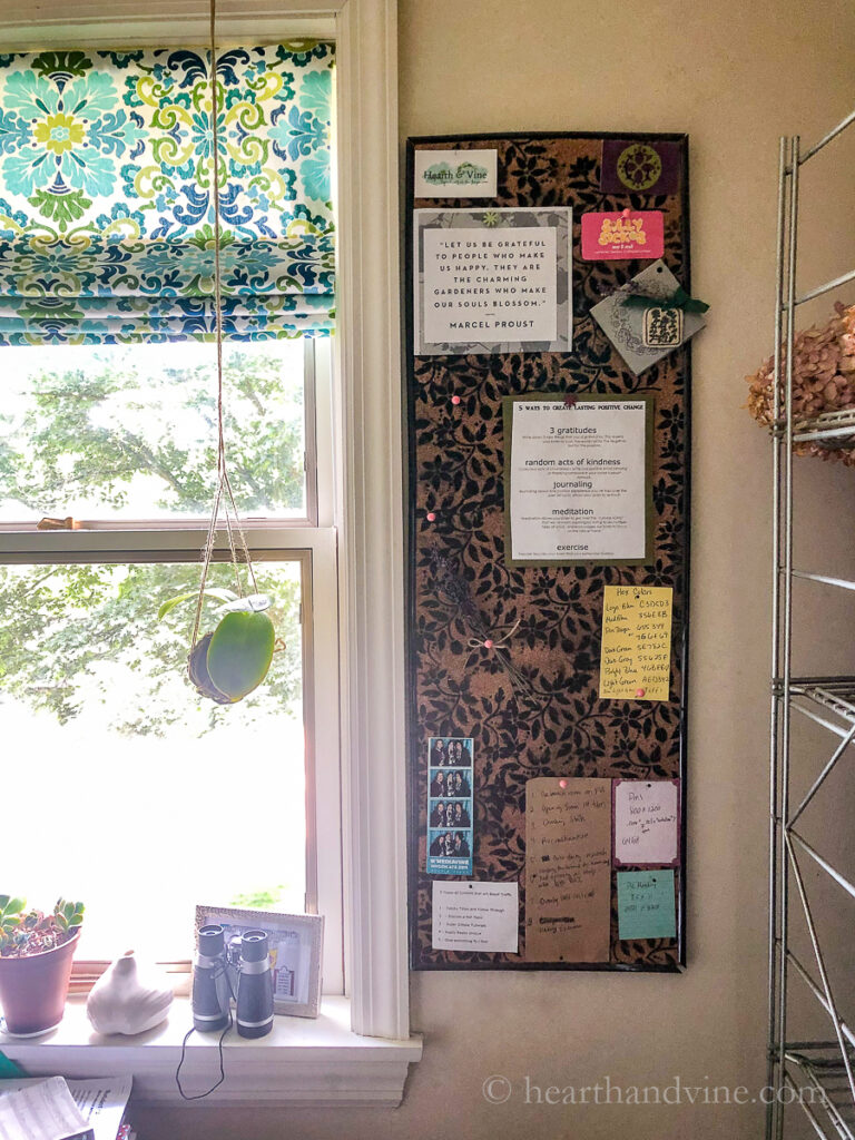DIY bulletin board hung vertically on the wall next to a window with notes pinned on.