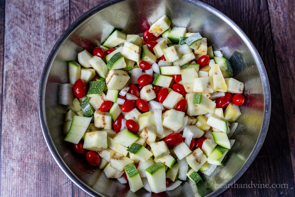 Metal mixing bowl with chopped zucchini, eggplant, onions, grape tomatoes and garlic cloves.