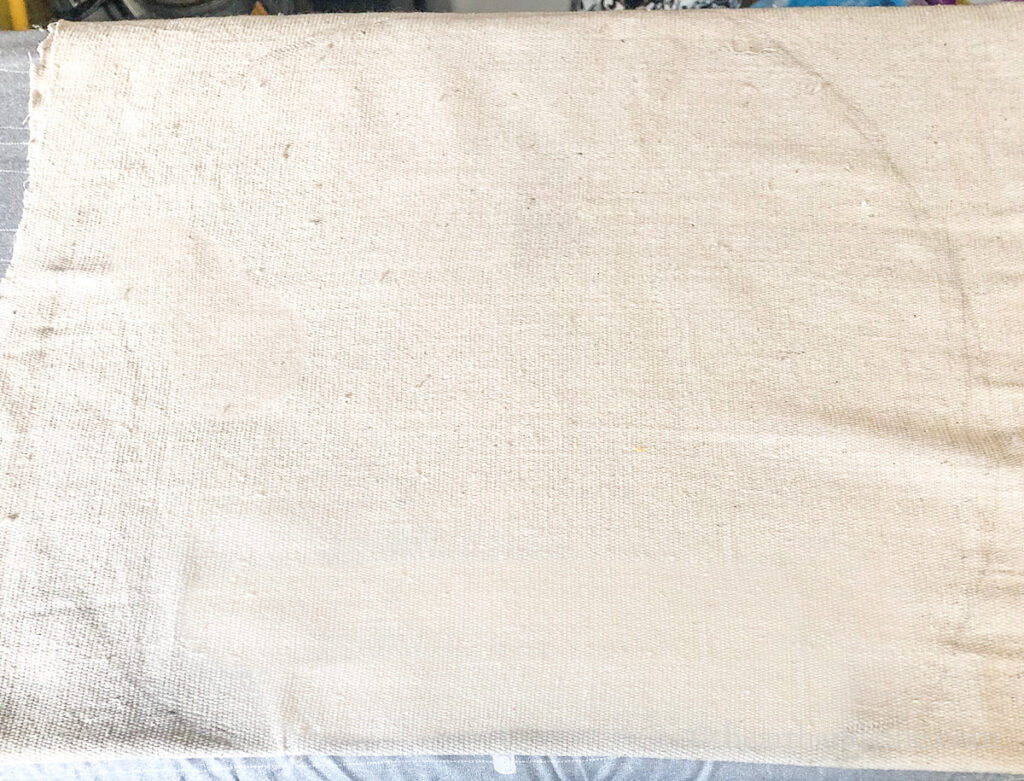 Drop cloth fabric folded and pumpkin shape traced in pencil.