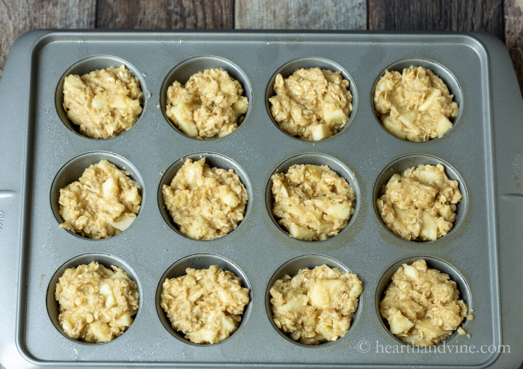 Apple muffin with oats batter in muffing tins before baking.