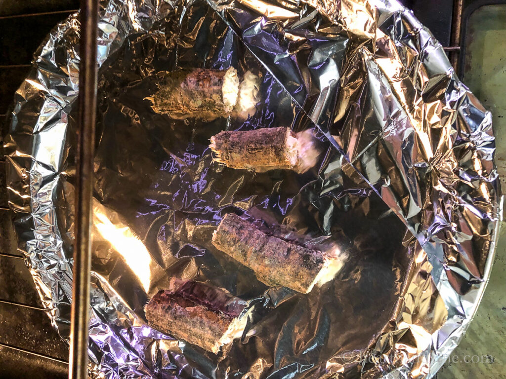 Cut pieces of a tree branch on foil in the oven.