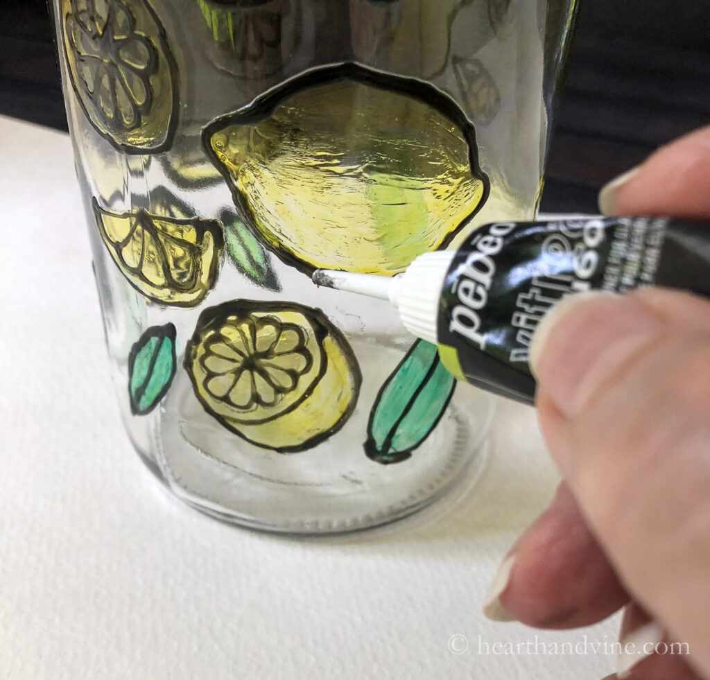 Using black paint outliner on bottle to outline glass paint pattern.