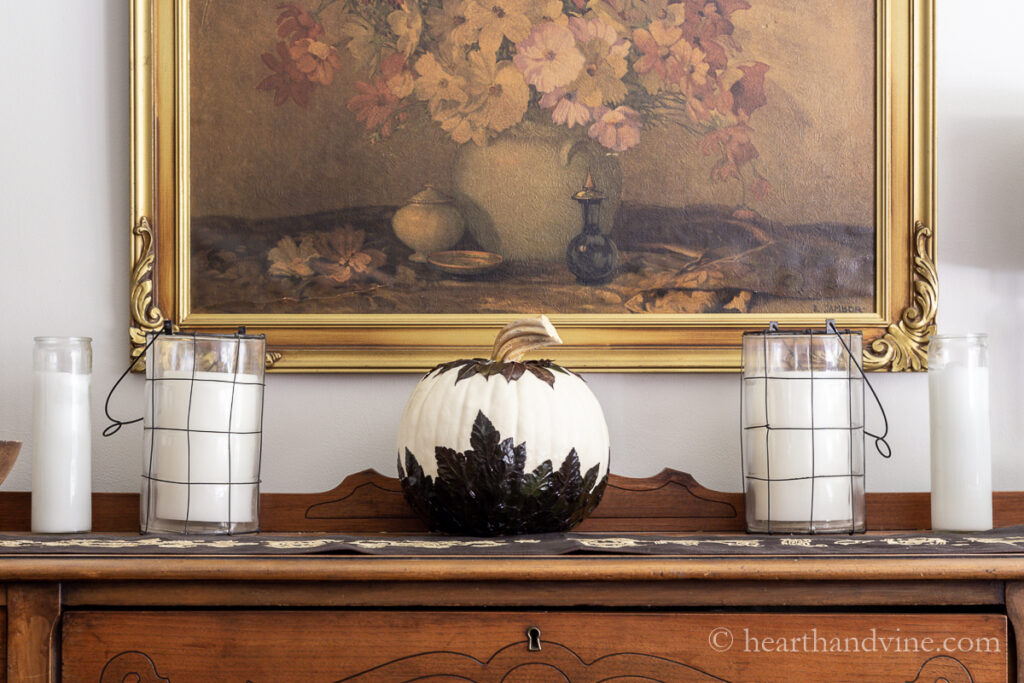 White pumpkin decorated with leaves on a buffet flanked with two candles on each side.