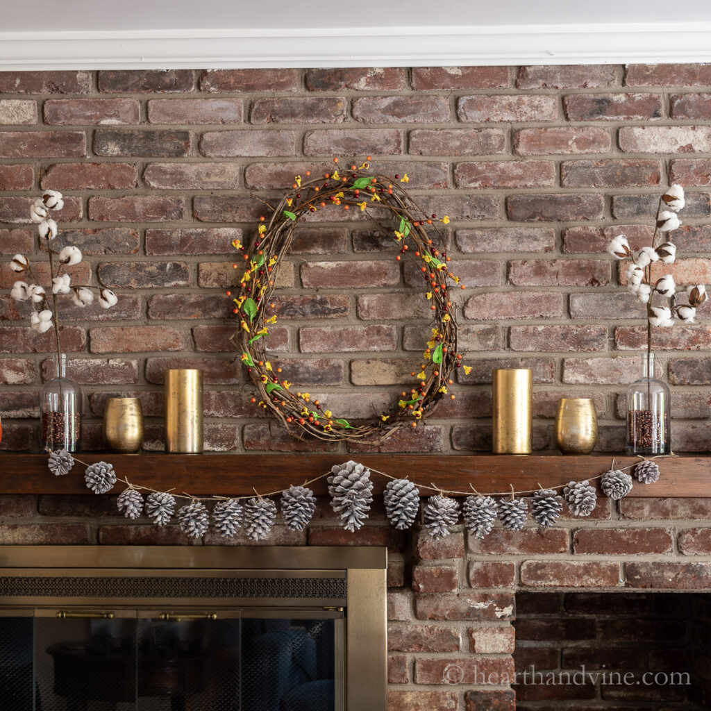 Fall mantel with pinecone garland, gold mercury glass, grapevine and bittersweet wreath and cotton stems.