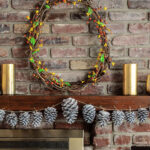 Fall mantel with bittersweet grapevine wreath, whitewashed pinecone garland and gold mercury glass candle holders.